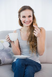 Cheerful young woman sitting on sofa holding cup and cookie