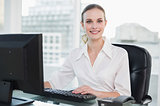 Smiling businesswoman sitting at desk looking at camera