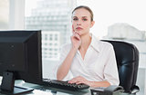 Thoughtful businesswoman sitting at desk looking at camera