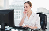 Thoughtful businesswoman sitting at desk looking at computer