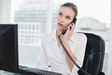 Thoughtful businesswoman sitting at desk on the phone