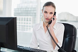 Stern businesswoman sitting at desk on the phone looking at camera