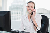 Smiling businesswoman sitting at desk on the phone looking at camera