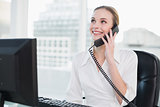 Smiling businesswoman sitting at desk on the phone