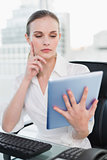 Thoughtful businesswoman sitting at desk using tablet pc
