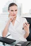 Stern businesswoman sitting at desk sending a text