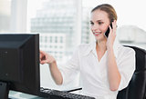 Happy businesswoman sitting at desk talking on smartphone pointing to screen