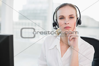 Thoughtful call centre agent looking at camera