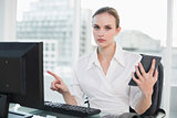 Frowning businesswoman holding calculator sitting at desk looking at camera