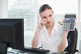 Frowning businesswoman showing calculator sitting at desk