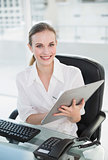 Happy businesswoman writing on clipboard sitting at desk
