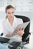 Serious businesswoman writing on clipboard sitting at desk looking at camera