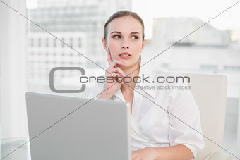 Thoughtful businesswoman using laptop