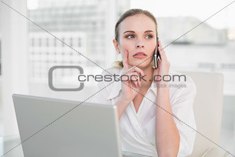 Thoughtful businesswoman using laptop and making a call