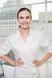 Confident businesswoman smiling at camera with hands on hips
