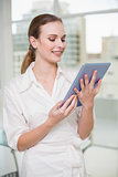 Smiling businesswoman holding her tablet pc