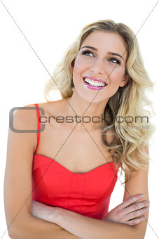 Thoughtful smiling blonde model posing with arms crossed