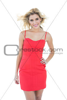 Happy smiling blonde model posing with hand on hips
