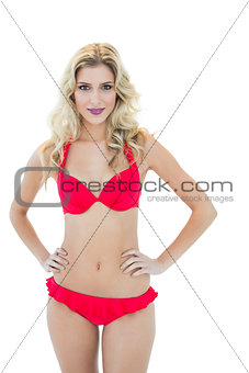 Attractive blonde model posing with hands on hips wearing bikini