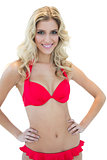 Openly smiling blonde model posing with hands on hips in red bikini