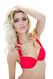 Sexy blonde model in red bikini looking mysteriously at camera