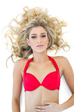 Gorgeous blonde model wearing red bikini looking at camera