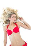 Passionate blonde model wearing red bikini smiling at camera