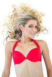 Cute blonde model wearing red bikini smiling at camera