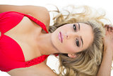 Beautiful blonde model wearing red bikini looking at camera