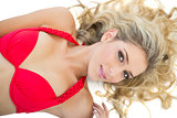 Cute blonde model wearing red bikini smiling seductively at camera