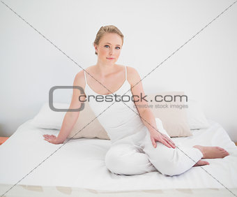 Natural peaceful blonde sitting on bed