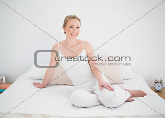 Natural smiling blonde sitting on bed