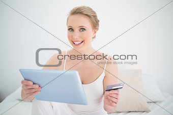 Natural smiling blonde holding tablet and credit card
