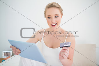 Natural cheerful blonde holding tablet and credit card