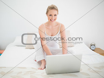 Natural happy blonde using laptop while sitting on bed
