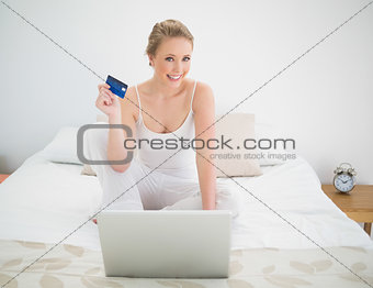 Natural cheerful blonde holding credit card and sitting in front of laptop