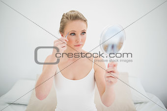 Natural serious blonde holding mirror and using tweezers