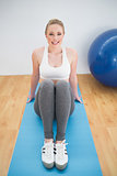 Smiling sporty blonde sitting on exercise mat