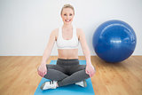 Smiling sporty blonde sitting cross legged on exercise mat