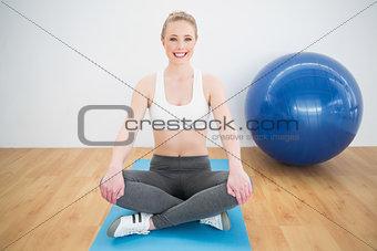 Smiling sporty blonde sitting cross legged on exercise mat
