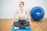 Content sporty blonde sitting cross legged on exercise mat