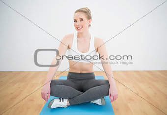 Gleeful sporty blonde sitting cross legged on exercise mat