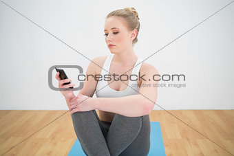 Attractive sporty blonde looking at smartphone