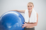 Cheerful sporty blonde with towel around her neck holding exercise ball