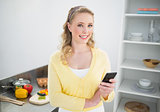 Smiling cute blonde holding smartphone
