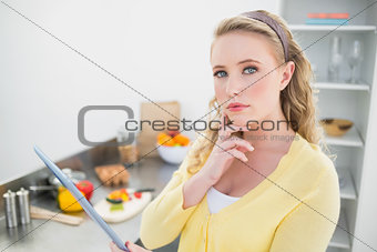 Thoughtful cute blonde holding tablet
