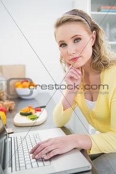 Thoughtful cute blonde using laptop