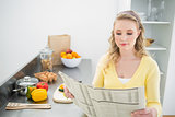 Content cute blonde reading newspaper