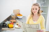 Content cute blonde reading newspaper
