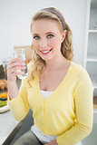 Happy cute blonde holding a glass of water